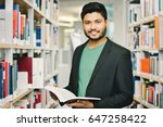 Small photo of Happy indian male student at the library
