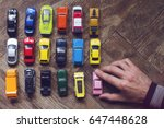 Stock photo horizontal top view of male hand arranging an assorted metal colorful toy car collection on brown 647448628
