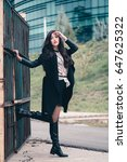 Small photo of Tall fancy young woman with natural curly hair posing seductive holding the steel gate. Dressed in knee-high leather boots, long coat and mini skirt holding mouth ajar and having wondering expression