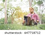 Small photo of Selective focus,Young man sitting on grass against a tree. Handsome guy repose in nature,copy space.