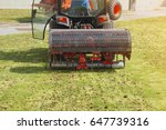 Small photo of Gardener Operating Soil Aeration Machine on Grass Lawn