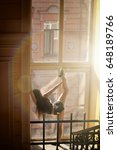Small photo of Young woman window acrobatics twine rays of sun staircase morning