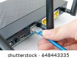 man plugs internet cable into... | Shutterstock . vector #648443335