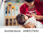 mom and baby feed a milk by... | Shutterstock . vector #648517642