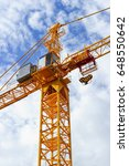 Small photo of Orange construction tower crane with jib and hook isolated on blue sky with white clouds background, detail