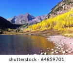Beautiful Maroon Bells with golden aspens in the Rocky Mountains of Colorado at dawn - stock photo