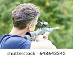 Small photo of Rear view shot of a man with airgun practicing at the shooting range.