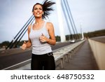 pretty female jogger running... | Shutterstock . vector #648750532