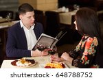 cheerful couple with menu in a... | Shutterstock . vector #648788752