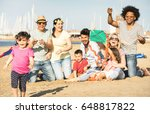 Small photo of Happy multiracial families and children playing together with kite at beach vacation - Multicultural summer joy concept with mixed race people having candid genuine fun - Warm afternoon color tones