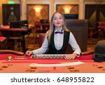 Small photo of Cute lady casino dealer at poker table.