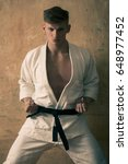 Small photo of karate or aikido man training in white kimono and black belt on beige background