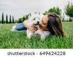Stock photo beautiful young woman playing with her little west highland white terrier in a park outdoors 649624228