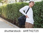 back pain man carrying heavy bag | Shutterstock . vector #649742725