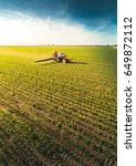 tractor spraying pesticides on... | Shutterstock . vector #649872112