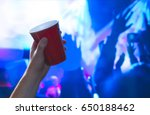 Stock photo young man holding red party cup in nightclub dance floor alcohol container in hand in disco 650188462