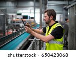 attentive factory worker using... | Shutterstock . vector #650423068