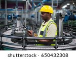 factory worker using a digital... | Shutterstock . vector #650432308