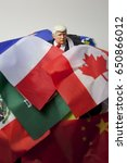 Small photo of Caricature of United States President Donald Trump buried in a pile of world flags - overwhelmed - global issues concept - action figure toy