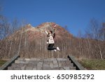 Small photo of Happy girl jump with mountain background. A girl is a female human from birth through childhood and adolescence to attainment of adulthood when she becomes a woman. Also be used to mean a young woman.