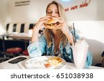 young woman eating burger in... | Shutterstock . vector #651038938