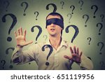 Small photo of Portrait blindfolded man stretching his arms out walking through many question marks