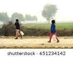 Small photo of BAUND KALAN, BHIWANI, HARYANA - 23 DECEMBER 2015: Two local Indian girls going to the field for work in the morning in the village of Baund Kalan in Bhiwani district, Haryana.