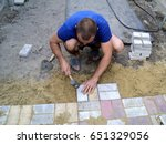 a worker lays paving slabs in... | Shutterstock . vector #651329056
