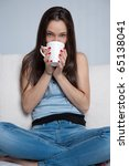 Attractive girl sitting on a sofa drinking from a mug - stock photo