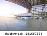 Stock photo roll out of the aircraft from the hangar by a tractor after repair 651657985