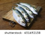 Stock photo mackerel fish on wooden chopping board with dramatic light and vignette effect 651692158