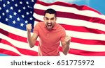Small photo of emotion, aggression, patriotism, gesture and people concept - angry young man showing fists over american flag