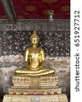 Small photo of Golden buddha stature on background vintage wall