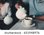man pours tea from teapot into... | Shutterstock . vector #651948976