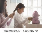 mother styling hair of daughter ... | Shutterstock . vector #652020772