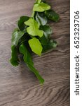 Small photo of Kafir lime leaves on the wood background