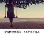 Girl Swinging On A Sandy Beach...