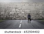 businessman facing a big stone... | Shutterstock . vector #652504402
