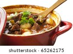 Beef stew in a red crock pot, ready to serve. - stock photo