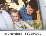 mother securing her toddler... | Shutterstock . vector #652654072