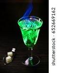 Small photo of Burning absinthe in glass and spoon with white sugar cubes on dark table background