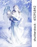 a beautiful Christmas angel over blue winter background - stock photo