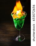 Small photo of Burning absinthe on dark table background