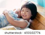 little sister hugging her... | Shutterstock . vector #653102776