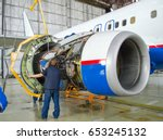 Stock photo replacing the engine on the plane working people tap concept maintenance of aircraft 653245132