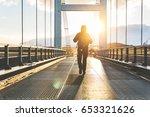 man walking on bridge at sunset.... | Shutterstock . vector #653321626