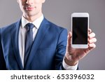 young male hand holding phone | Shutterstock . vector #653396032