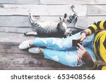 Stock photo hipster lifestyle girl in jeans with black smart phone and retro camera with cat sit on the 653408566
