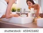 young woman washing her face... | Shutterstock . vector #653421682