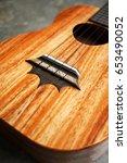 Small photo of Detail of ukulele bridge and black nylon strings on concrete background.